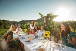 Menschen an Tisch im Weingarten